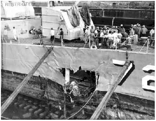 Taken in dry dock Sasebo, Japan. Japanese yard workers assembled for briefing on bow removal. Severe mine damage below water line from mine explosion.
